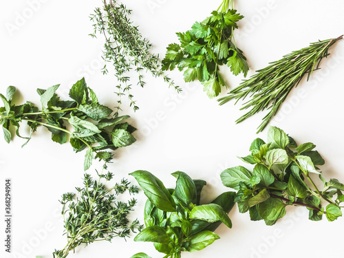 Fototapeta Flat-lay of various fresh green kitchen herbs. Parsley, mint, savory, basil, rosemary, thyme over white background, top view. Spring or summer healthy vegan cooking concept obraz