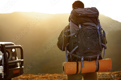 Portrait of a young traveler man in hiking equipment standing near his off-road Wallpaper Mural