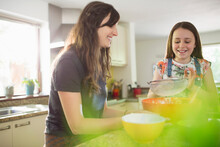 Happy Mother And Daughter Baking In Kitchen