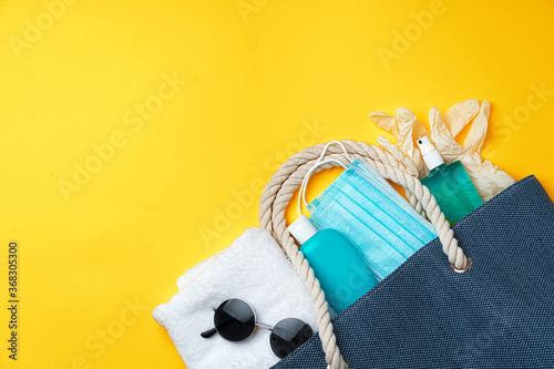 Blue beach bag with beach accessories and protective mask on yellow background