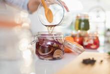 Woman Pickling Red Onions In Jar
