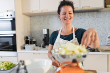Smiling Woman Weighing Apples For Baking In Kitchen