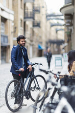 Businessman With Bicycle On Ci...