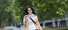 Smiling Woman Using Smart Phone In Park