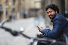 Portrait Smiling Businessman With Smart Phone On City Street