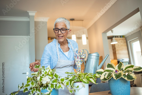 Senior Woman With Green Plants and Flowers at home Canvas Print