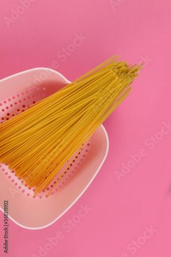 Różowy durszlak z surowym zbożowym makaronem na spaghetti bolognese na różowym tle
