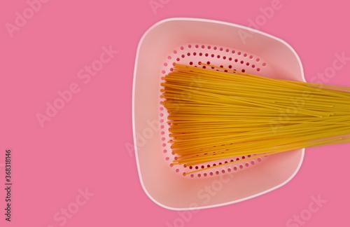 Różowy durszlak z zbożowym makaronem na spaghetti bolognese