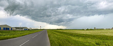 Countryside Road And Dark Stormy Sky With Ominous Clouds On Horizon. Panoramic View