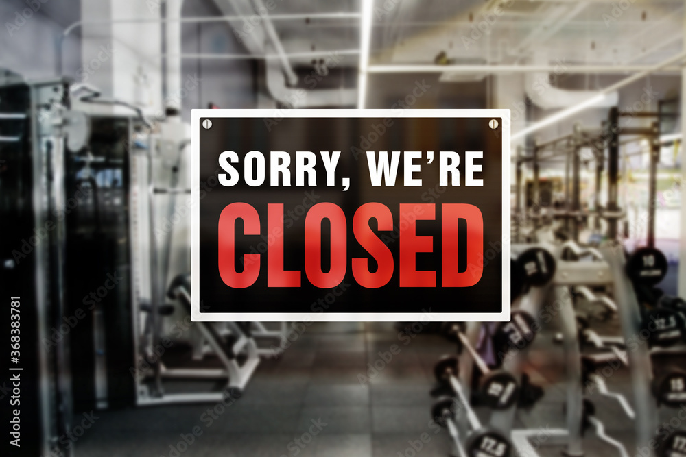 Fototapeta Image of a blurred gym background with closed sign in front. Closure or bankruptcy of gym or fitness center.