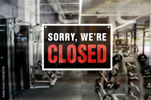Fototapeta Image of a blurred gym background with closed sign in front. Closure or bankruptcy of gym or fitness center. obraz