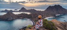 Young Traveller Sitting And Relaxing On Top Of Padar Island At Sunset, Komodo National Park In Indonesia. Panoramic Banner Portion
