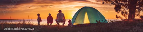 Fototapeta Family resting with tent in nature at sunset obraz