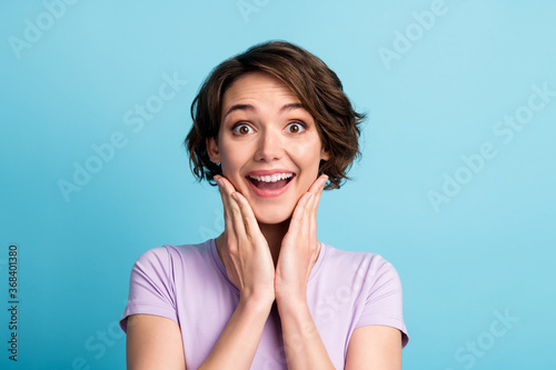 Portrait of astonished positive cheerful girl impressed wonderful bargain novelty touch face hands wear good look clothes isolated over blue color background