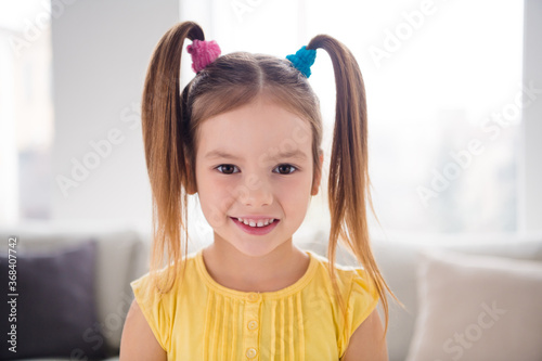 Close up photo of charming lovely little girl kid look in camera toothy smile in living room house indoors