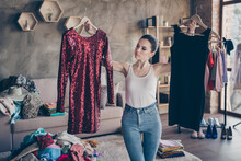 Portrait Of Her She Nice Attractive Doubtful Girl Holding In Hands Hangers Two New Chic Designer Couture Dress Comparing Preparing Party Wear In Modern Loft Industrial Interior Apartment