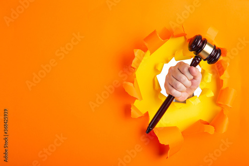 Photo Hand holding a judge's gavel through torn orange paper wall