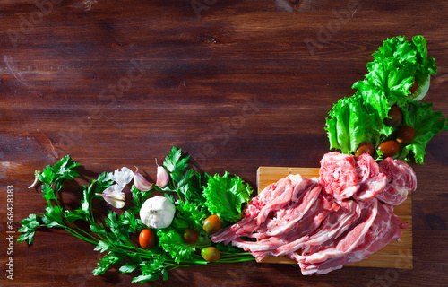 Fototapeta Natural wooden background with raw lamb chops, vegetables, greens and condiments.. obraz