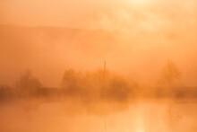 Sunrise Over Foggy Lake. Canes...