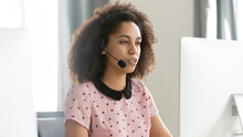 African American Female Call Center Operator In Wireless Headset Using Computer, Looking At Screen, Employee Consulting Client On Phone In Customer Support Service Office, Horizontal Photo Close Up