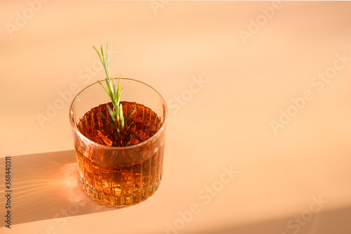 Fotografija One Glass of cold whiskey garnish rosemary on beige background with sunny shadow