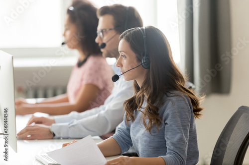 Call center agent in headset consulting client, woman in headphones working with documents, looking at computer screen, group employees sitting at workplace in customer support service office