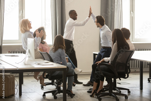 Obraz African American executive, team leader with colleague giving high five during briefing, smiling employees engaged in team building activity, celebrating achievement, business win or good result - fototapety do salonu