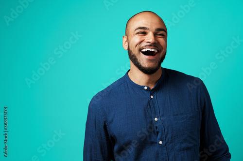 Joyful dark-skinned man laughing against turquoise background Fototapeta