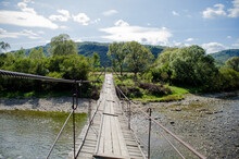 View Of A Rocky Shallow Mountain River From A Tall Old Wooden Suspension Bridge In Sunlight