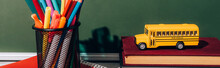 Horizontal Image Of School Bus Model On Books Near Pen Holder With Stationery On Notebook Near Green Chalkboard