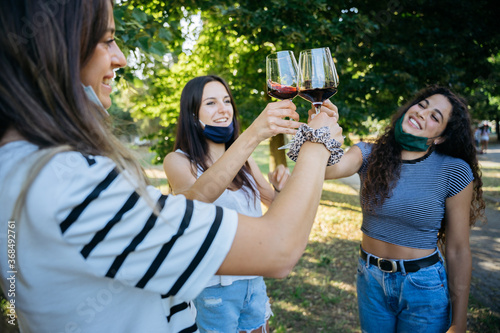 Photo Young millennial women toasting in a park with red wine glasses in a tasting - G