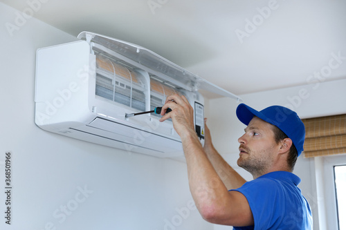 Obraz na plátně hvac services - technician installing air conditioner on the wall at home