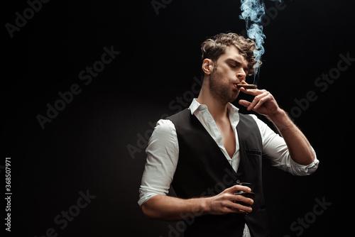 Fotografija Man in shirt and waistcoat smoking cigar and holding glass of whiskey isolated o