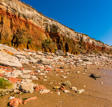 White And Orange Rockfalls Litter The Beach Beneath The White, Red And Orange Stratified Cliffs At Old Hunstanton, Norfolk, UK