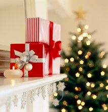 Christmas Gifts Presents On Living Room Mantel With Candle And Decorated Tree In Background. Beautiful, Elegant Holiday Home Interior Decor Decorations.
