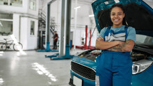 Truly Auto Motivated. Young African American Woman, Professional Female Mechanic Smiling At Camera, Leaning On A Car In Auto Repair Shop