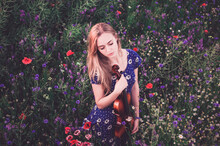 A Young Blonde European Thin Girl Stands In The Midst Of Very Tall Purple And Poppy Plant Hugs Herself With Her Eyes Closed Holding A Violin.Women's Blue Short Skin-tight Dress With White Daisy Print