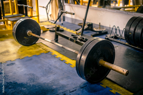 Valokuva A rusty olympic size barbell loaded with plates on rubber matting