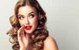 Beautiful girl with bright makeup and curly hair   telling a secret .Portrait  young happy woman who is calling to someone .Funny girl model  whispering about something. Expressive facial expressions