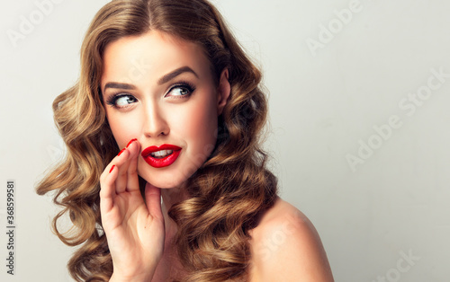 Obraz Beautiful girl with bright makeup and curly hair   telling a secret .Portrait  young happy woman who is calling to someone .Funny girl model  whispering about something. Expressive facial expressions - fototapety do salonu