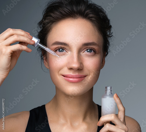 Obraz na plátne Woman applying  hyaluronic serum on fer face with pipette
