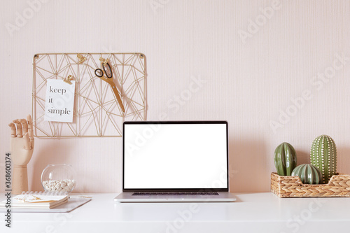 Obraz Laptop with blank white screen on office desk interior. Stylish gold workplace mockup table view.  - fototapety do salonu