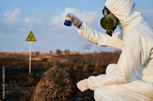 Valokuva Ecologist in suit, gas mask holding test tube with blue liquid while studying burnt grass and soil on scorched territory with biohazard sign