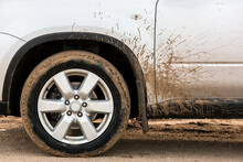 The Front Wheel Of A Dirty Car In The Sand Spattered The Fender And Driver's Door With Mud.