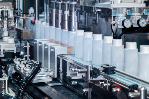 Obraz white plastic bottle moving on conveyor belt of auto capping and labeling machine at cosmetic and skin care manufacturing. cosmetic industry and ai technology machinery concept. - fototapety do salonu