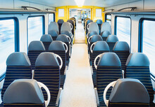 Train Interior With Empty Chairs. German Passenger Train Carriage In Motion