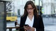 Concentrated business lady in eyeglasses and office clothing talking on smartphone while walking at big city. Charming female with brown hair having working conversation on mobile.