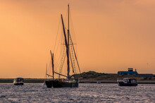A View Of Boats Moored At Blakeney Point, Norfolk Looking Towards The Lifeboat Station In The Distance Just Before Sunset