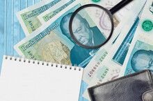 5 British Pounds Bills And Magnifying Glass With Black Purse And Notepad. Concept Of Counterfeit Money. Search For Differences In Details On Money Bills To Detect Fake