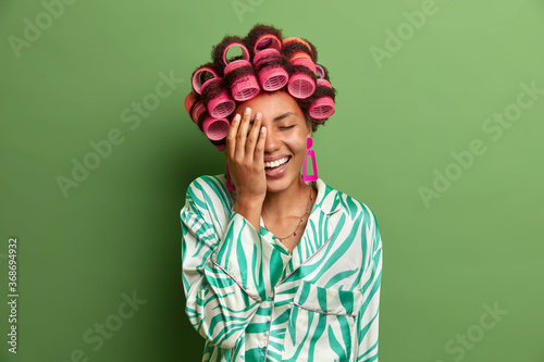 Happy dark skinned woman makes face palm, cannot stop laughing after hearing joke, expresses positive emotions, wears hair curlers to look fabulous at tomorrow party, dressed in silk gown Canvas Print